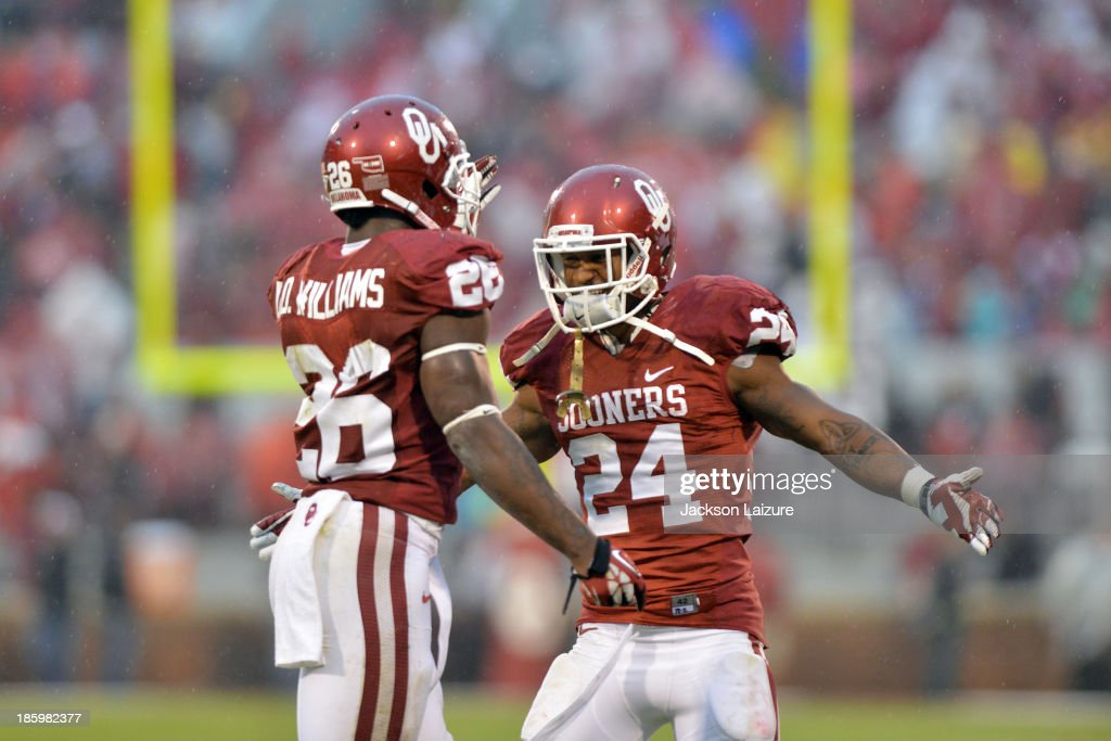 Running back Brennan Clay #24 celebrates a touchdown with Damien Williams #26 of the Oklahoma Sooners during their win against the Texas Tech Red Raiders on October 26, 2013 at Gaylord Family Oklahoma Memorial Stadium in Norman, Oklahoma.
