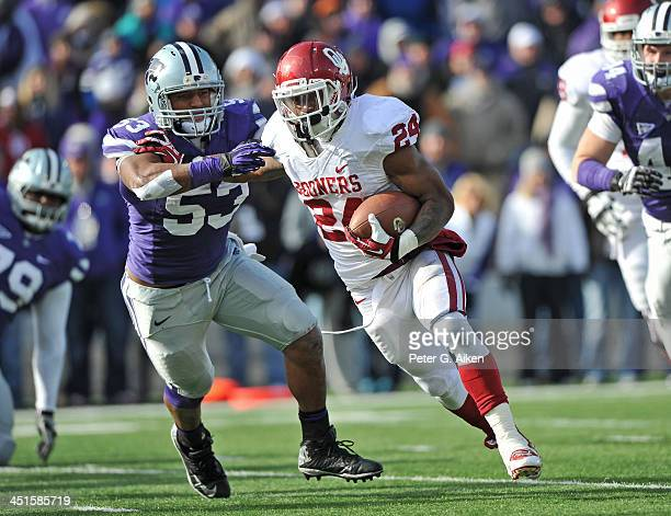 Running back Brennan Clay of the Oklahoma Sooners rushes for a threeyard touchdown past linebacker Blake Slaughter of the Kansas State Wildcats...