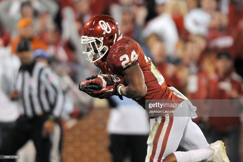 Running back Brennan Clay #24 of the Oklahoma Sooners scores the game-winning touchdown in overtime in their game against the Oklahoma State Cowboys on November 24, 2012 at The Gaylord Family Oklahoma Memorial Stadium in Norman, Oklahoma.