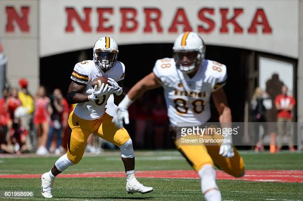 Running back Brian Hill runs behind tight end Jacob Hollister of the Wyoming Cowboys against the Nebraska Cornhuskers at Memorial Stadium on...