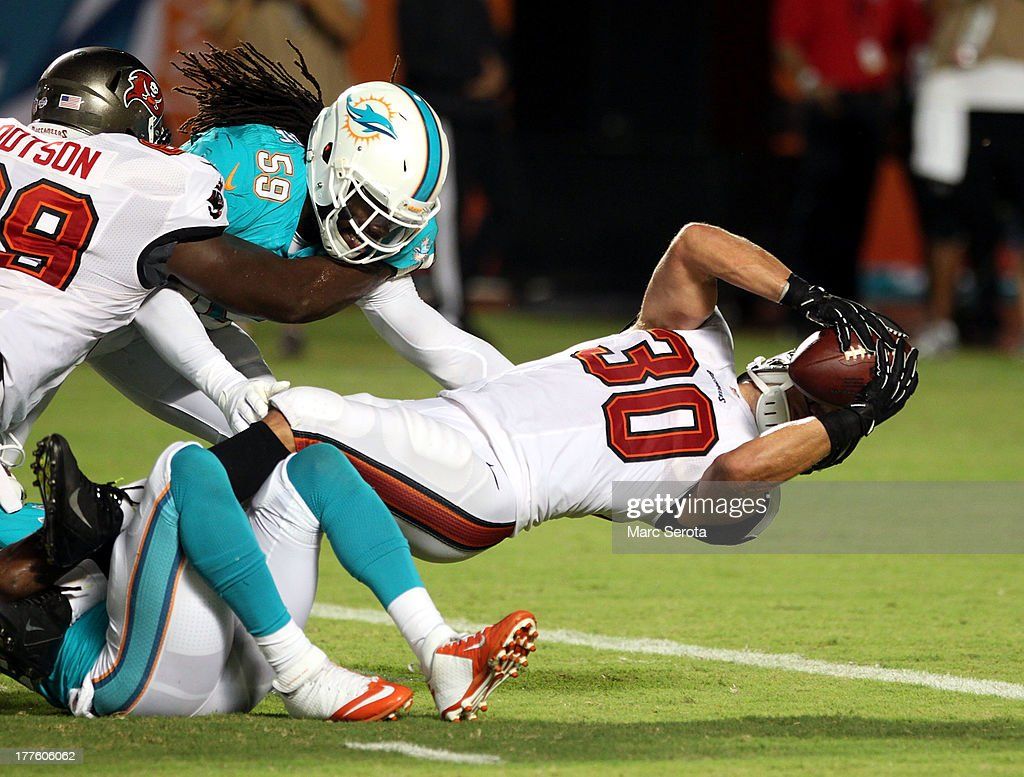 Running back <a gi-track='captionPersonalityLinkClicked' href=/galleries/search?phrase=Brian+Leonard&family=editorial&specificpeople=2155782 ng-click='$event.stopPropagation()'>Brian Leonard</a> #30 of the Tampa Bay Buccaneers scores a touchdown against the Miami Dolphins at Sun Life Stadium on August 24, 2013 in Miami Gardens, Florida.