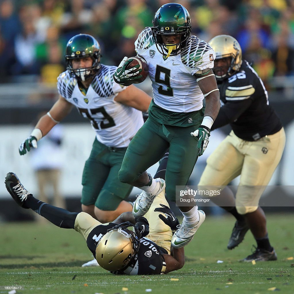 Running back Byron Marshall #9 of the Oregon Ducks eludes defender defensive back Chidobe Awuzie #4 of the Colorado Buffaloes at Folsom Field on October 5, 2013 in Boulder, Colorado. The Ducks defeated the Buffs 57-16.