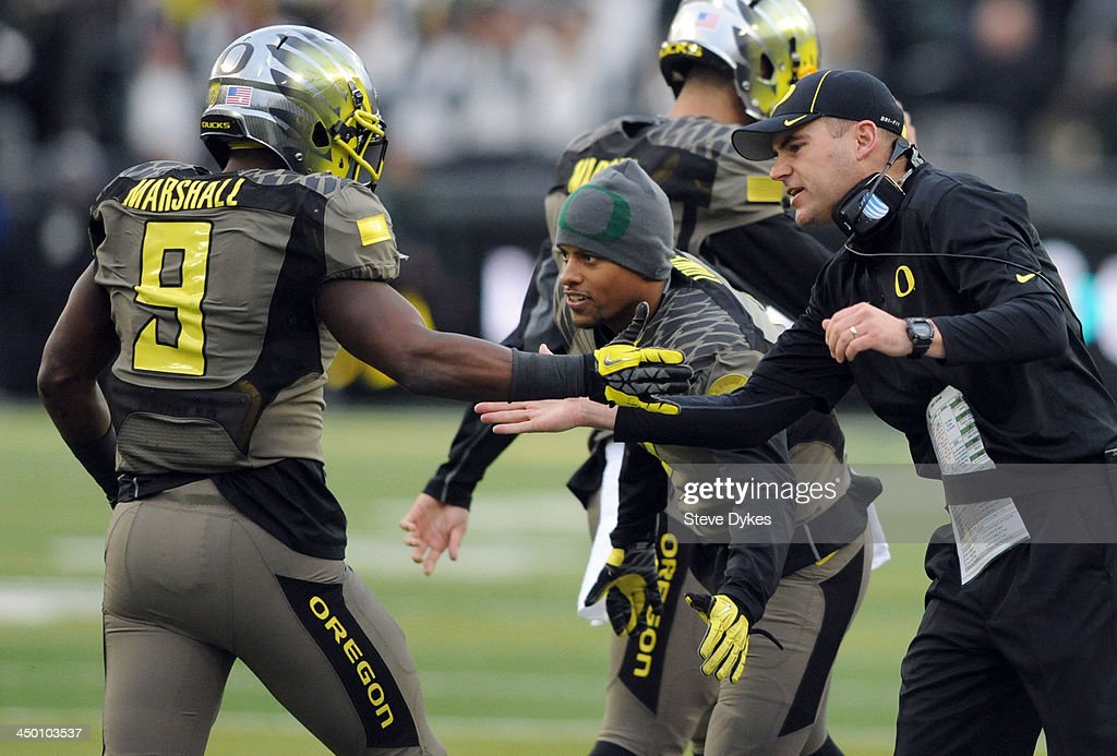 Running back Byron Marshall #9 of the Oregon Ducks is greeted on the sidelines by head coach Mark Helfrich after scoring a touchdown during the third quarter of the game against the Utah Utes at Autzen Stadium on November 16, 2013 in Eugene, Oregon.