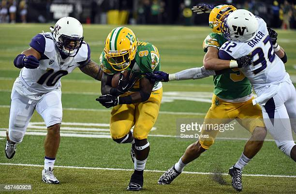 Running back Byron Marshall of the Oregon Ducks runs past linebacker John Timu and defensive back Budda Baker of the Washington Huskies on his way to...