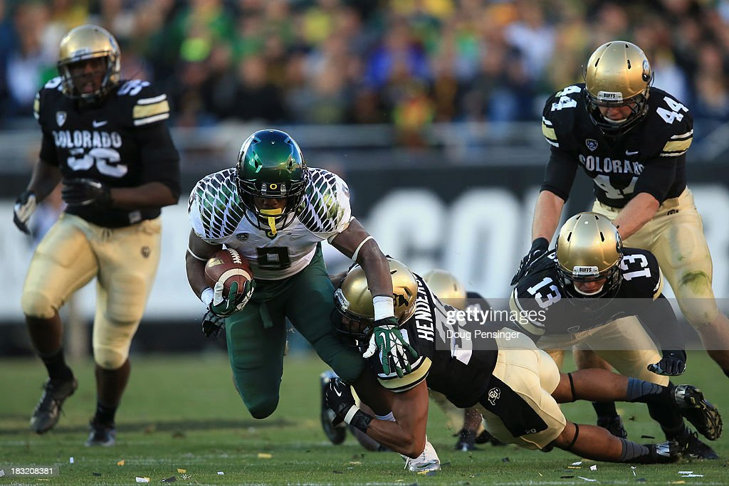 Running back Byron Marshall #9 of the Oregon Ducks rushes with the ball and tries to break a tackle by defensive back <a gi-track='captionPersonalityLinkClicked' href=/galleries/search?phrase=Greg+Henderson&family=editorial&specificpeople=171423 ng-click='$event.stopPropagation()'>Greg Henderson</a> #20 of the Colorado Buffaloes at Folsom Field on October 5, 2013 in Boulder, Colorado. The Ducks defeated the Buffs 57-16.