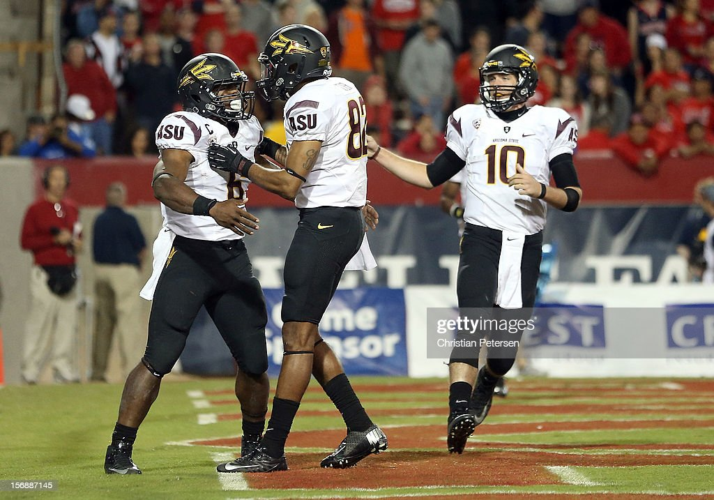 Running back Cameron Marshall #6 of the Arizona State Sun Devils celebrates with wide receiver Kevin Ozier #82 and quarterback Taylor Kelly #10 after scoring on a 8 yard rushing touchdown against the Arizona Wildcats during the fourth quarter of the college football game at Arizona Stadium on November 23, 2012 in Tucson, Arizona. The Sun Devils defeated the Wildcats 41-34.
