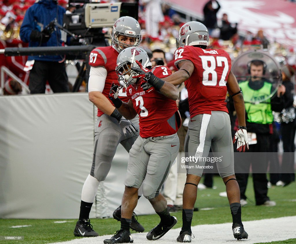 Running back Carl Winston #3 of the Washington State Cougars reacts with teammates Andrei Lintz #87 and Bobby Ratliff #82 after his fourth quarter touchdown during the game against the Washington Huskies at Martin Stadium on November 23, 2012 in Pullman, Washington.