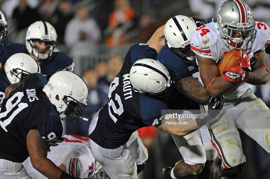 Running back Carlos Hyde #34 of the Ohio State Buckeyes is pulled down by Penn State Nittany Lions defenders in the fourth quarter at Beaver Stadium on October 27, 2012 in State College, Pennsylvania. The Ohio State Buckeyes won, 35-23.