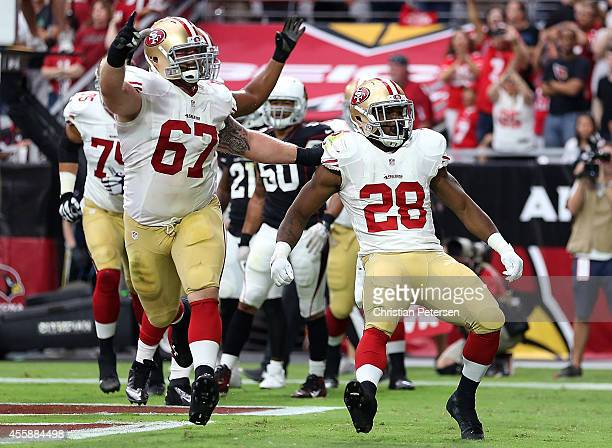 Running back Carlos Hyde of the San Francisco 49ers celebrates a secondquarter touchdown with center Daniel Kilgore during the NFL game against the...