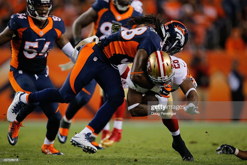Running back <a gi-track='captionPersonalityLinkClicked' href=/galleries/search?phrase=Carlos+Hyde&family=editorial&specificpeople=7244458 ng-click='$event.stopPropagation()'>Carlos Hyde</a> #28 of the San Francisco 49ers is tackled by strong safety <a gi-track='captionPersonalityLinkClicked' href=/galleries/search?phrase=Quinton+Carter&family=editorial&specificpeople=5631827 ng-click='$event.stopPropagation()'>Quinton Carter</a> #38 of the Denver Broncos during a game at Sports Authority Field at Mile High on October 19, 2014 in Denver, Colorado.