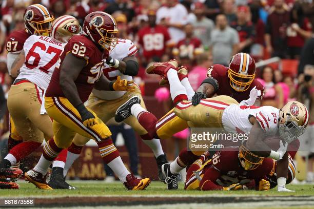 Running back Carlos Hyde of the San Francisco 49ers is tackled by outside linebacker Preston Smith of the Washington Redskins during the first half...