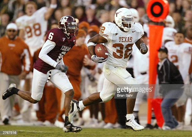 Running back Cedric Benson of the Texas Longhorns runs for a touchdown with defensive back Bryant Singleton of the Texas AM Aggies trailing behind...