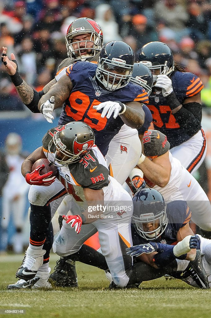 Running back Charles Sims #34 of the Tampa Bay Buccaneers carries the ball ahead of defensive tackle Ego Ferguson #95 of the Chicago Bears in the second quarter at Soldier Field on November 23, 2014 in Chicago, Illinois. The Chicago Bears defeat the Tampa Bay Buccaneers 21-13.