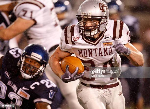 Running back Chase Reynolds of the Montana Grizzlies eludes linebacker Osayi Osunde of the Villanova Wildcats during the NCAA FCS Championship game...
