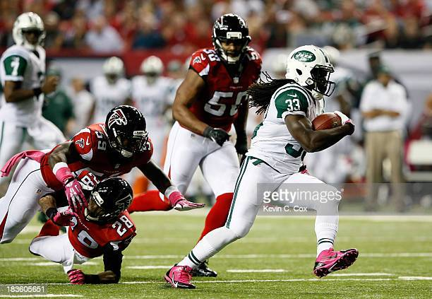 Running back Chris Ivory of the New York Jets breaks a tackle by outside linebacker Joplo Bartu and free safety Thomas DeCoud of the Atlanta Falcons...
