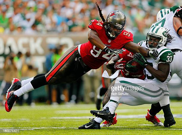 Running back Chris Ivory of the New York Jets runs for a first down as defensive end Adrian Clayborn of the Tampa Bay Buccaneers attempts to bring...