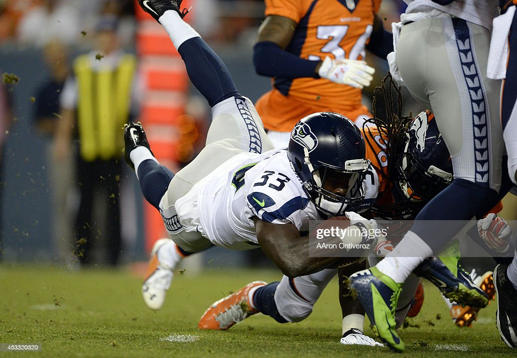 Running back <a gi-track='captionPersonalityLinkClicked' href=/galleries/search?phrase=Christine+Michael&family=editorial&specificpeople=6235349 ng-click='$event.stopPropagation()'>Christine Michael</a> (33) of the Seattle Seahawks takes the ball to the one yard line and gets hit by strong safety <a gi-track='captionPersonalityLinkClicked' href=/galleries/search?phrase=Quinton+Carter&family=editorial&specificpeople=5631827 ng-click='$event.stopPropagation()'>Quinton Carter</a> (38) of the Denver Broncos making it a first and goal during the first half. The Denver Broncos vs the Seattle Seahawks At Sports Authority Field at Mile High.