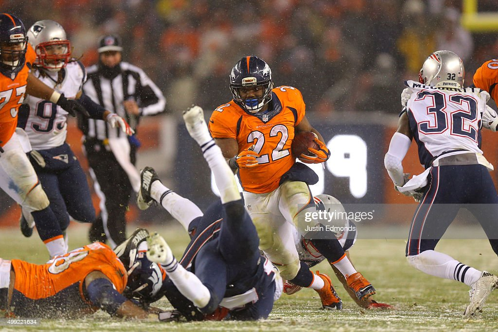 Running back C.J. Anderson #22 of the Denver Broncos carries the ball for an overtime touchdown to defeat the New England Patriots 30-24 at Sports Authority Field at Mile High on November 29, 2015 in Denver, Colorado.