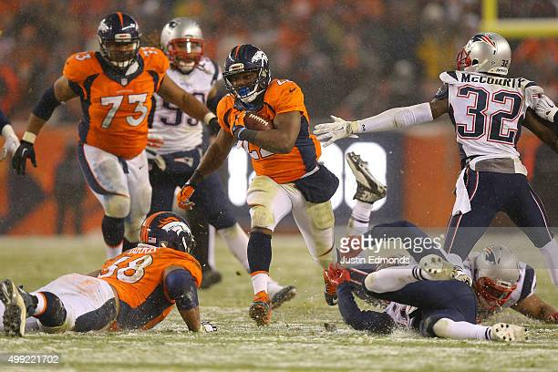 Running back CJ Anderson of the Denver Broncos carries the ball past free safety Devin McCourty of the New England Patriots for an overtime touchdown...