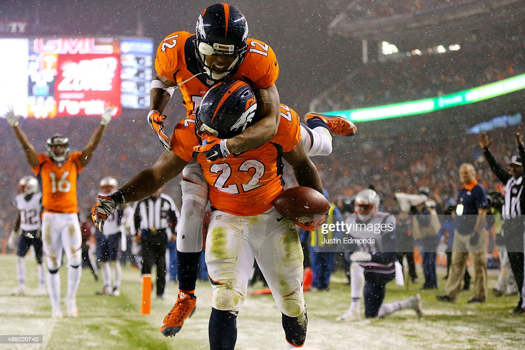 Running back C.J. Anderson #22 of the Denver Broncos celebrates with wide receiver Andre Caldwell #12 of the Denver Broncos after scoring a fourth quarter touchdown against the New England Patriots at Sports Authority Field at Mile High on November 29, 2015 in Denver, Colorado.