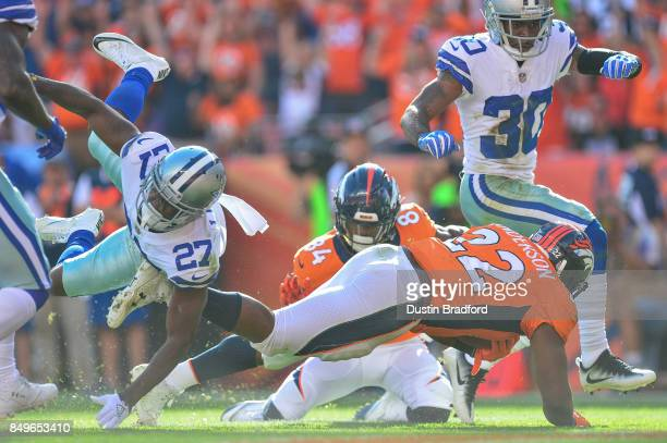 Running back CJ Anderson of the Denver Broncos dives across the goal line for a second quarter touchdown as cornerback Jourdan Lewis and cornerback...