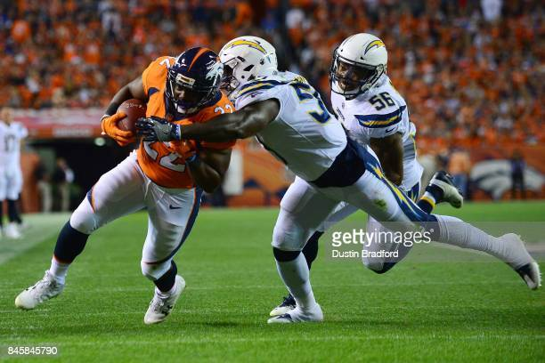 Running back CJ Anderson of the Denver Broncos is tackled by inside linebacker Jatavis Brown of the Los Angeles Chargers in the first quarter at...