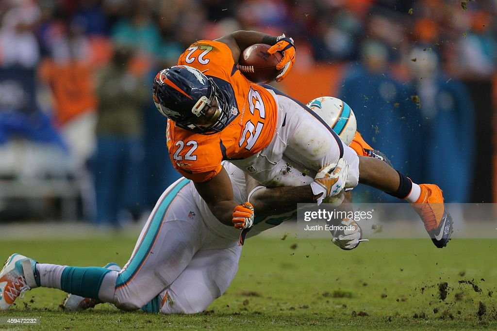 Running back CJ Anderson of the Denver Broncos is tackled by defensive tackle Randy Starks of the Miami Dolphins during a game at Sports Authority...