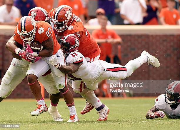 Running back CJ Fuller of the Clemson Tigers is pulled down by safety Josh Jones of the North Carolina State Wolfpack on October 15 2016 at Memorial...