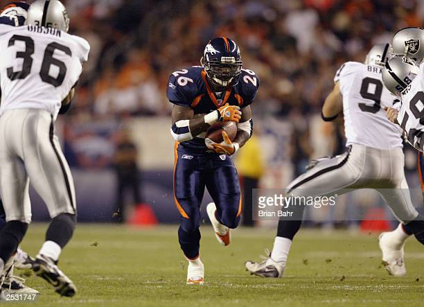Running back Clinton Portis of the Denver Broncos carries the ball against the Oakland Raiders on September 22 2003 at Invesco Field at Mile High in...