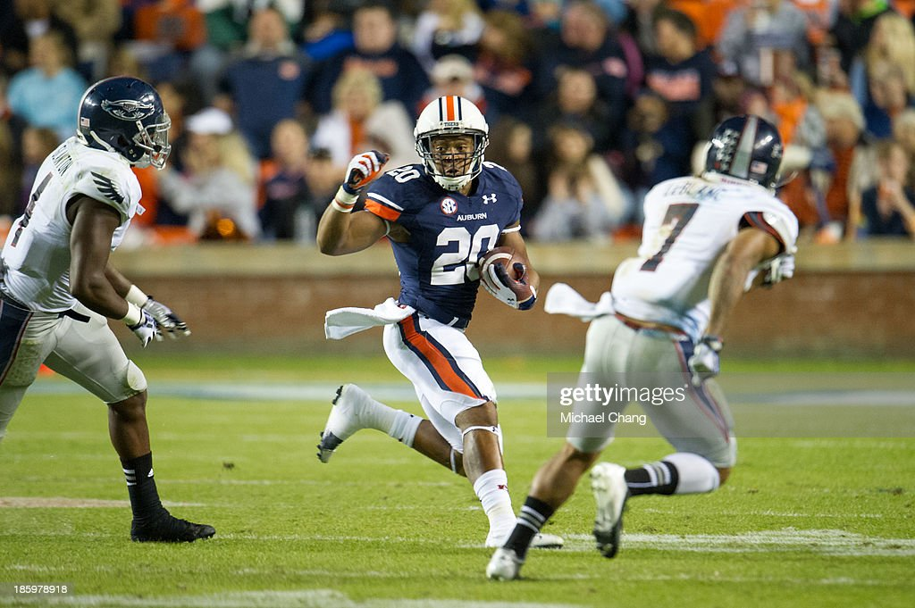 Running back Corey Grant #20 of the Auburn Tigers looks to maneuver by linebacker Adarius Glanton #4 and defensive back Cre'von LeBlanc #7 of the Florida Atlantic Owls on October 26, 2013 at Jordan-Hare Stadium in Auburn, Alabama. Auburn defeated Florida Atlantic 45-10.