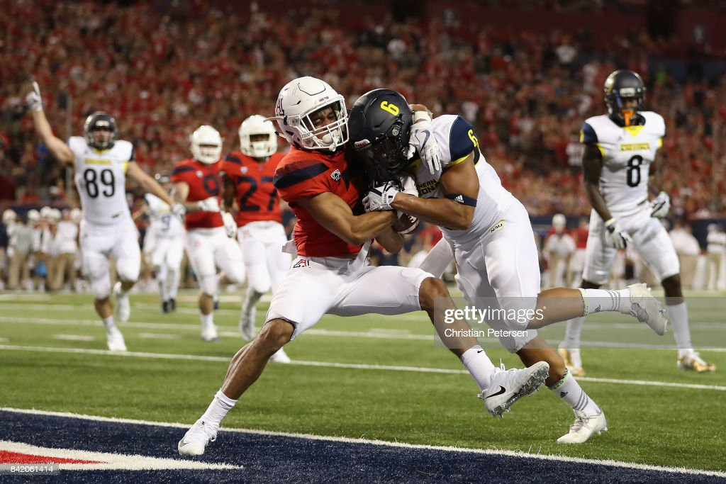 Running back Cory Young #6 of the Northern Arizona Lumberjacks scores on a seven yard rushing touchdown against cornerback Lorenzo Burns #2 of the Arizona Wildcats during the first half of the college football game at Arizona Stadium on September 2, 2017 in Tucson, Arizona.
