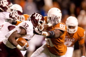 Running back Cyrus Gray of Texas AM holds off University of Texas defensive end Sam Acho during the second half at Darrell K RoyalTexas Memorial...