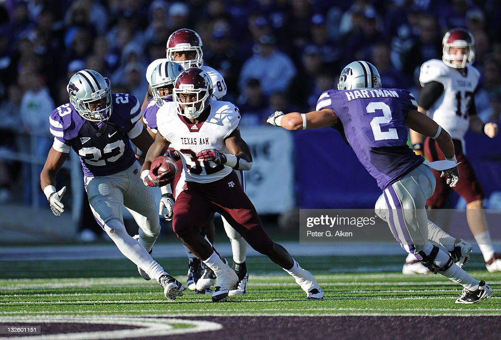 Running back Cyrus Gray #32 of the Texas A&M Aggies rushes up field past defenders Emmanuel Lamur #23 and Tysyn Hartman #2 of the Kansas State Wildcats during the first half on November 12, 2011 at Bill Snyder Family Stadium in Manhattan, Kansas.