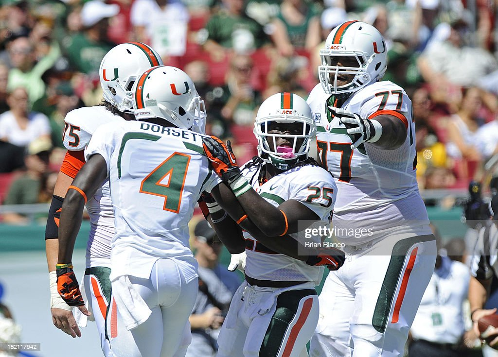Running back Dallas Crawford #25 of the Miami Hurricanes celebrates his first quarter touchdown with teammates, wide receiver Phillip Dorsett #4, offensive linesman <a gi-track='captionPersonalityLinkClicked' href=/galleries/search?phrase=Seantrel+Henderson&family=editorial&specificpeople=7084005 ng-click='$event.stopPropagation()'>Seantrel Henderson</a> #77 and offensive linesman Jared Wheeler #75 on September 28, 2013 at Raymond James Stadium in Tampa, Florida.