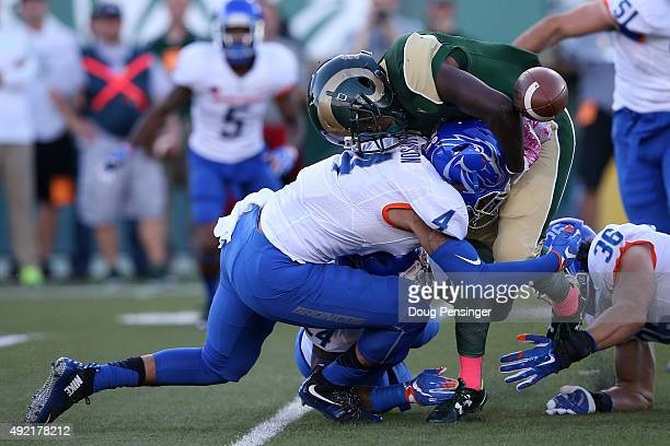 Running back Dalyn Dawkins of the Colorado State Rams fumbles the ball as he is tackled by Darian Thompson of the Boise State Broncos and was...