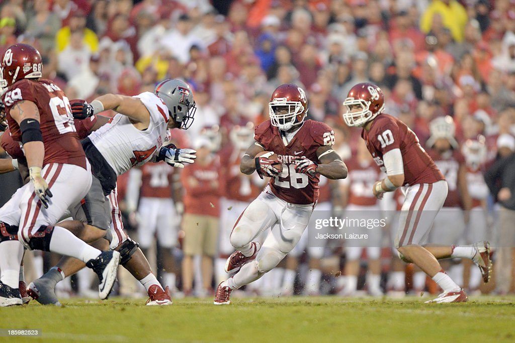 Running back Damien Williams #26 of the Oklahoma Sooners is pressured by defensive lineman Jackson Richards #43 of the Texas Tech Red Raiders during the Sooners' win on October 26, 2013 at Gaylord Family Oklahoma Memorial Stadium in Norman, Oklahoma.