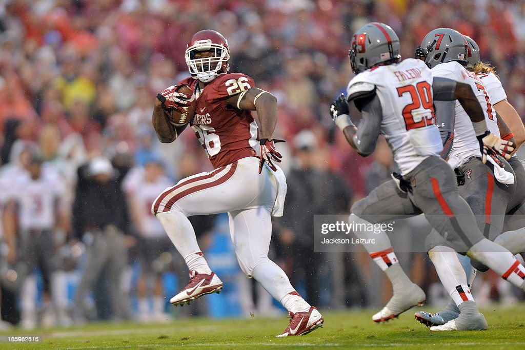 Running back Damien Williams #26 of the Oklahoma Sooners tries to out run linebacker <a gi-track='captionPersonalityLinkClicked' href=/galleries/search?phrase=Will+Smith+-+American+Football+Player+-+Born+1992&family=editorial&specificpeople=13424681 ng-click='$event.stopPropagation()'>Will Smith</a> #7 and defensive back Olaoluwa Falemi #29 of the Texas Tech Red Raiders during the Sooners' win on October 26, 2013 at Gaylord Family Oklahoma Memorial Stadium in Norman, Oklahoma.