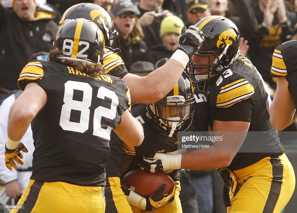 Running back Damon Bullock #5 of the Iowa Hawkeyes is congratulated by offesive lineman Austin Blythe #63 after soring a touchdown during the first quarter against the Northwestern Wildcats on October 26, 2013 at Kinnick Stadium in Iowa City, Iowa.