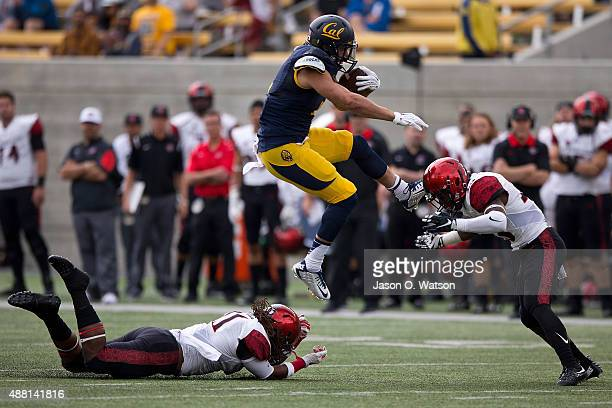 Running back Daniel Lasco of the California Golden Bears jumps past defensive back Na'im McGee of the San Diego State Aztecs into defensive back...