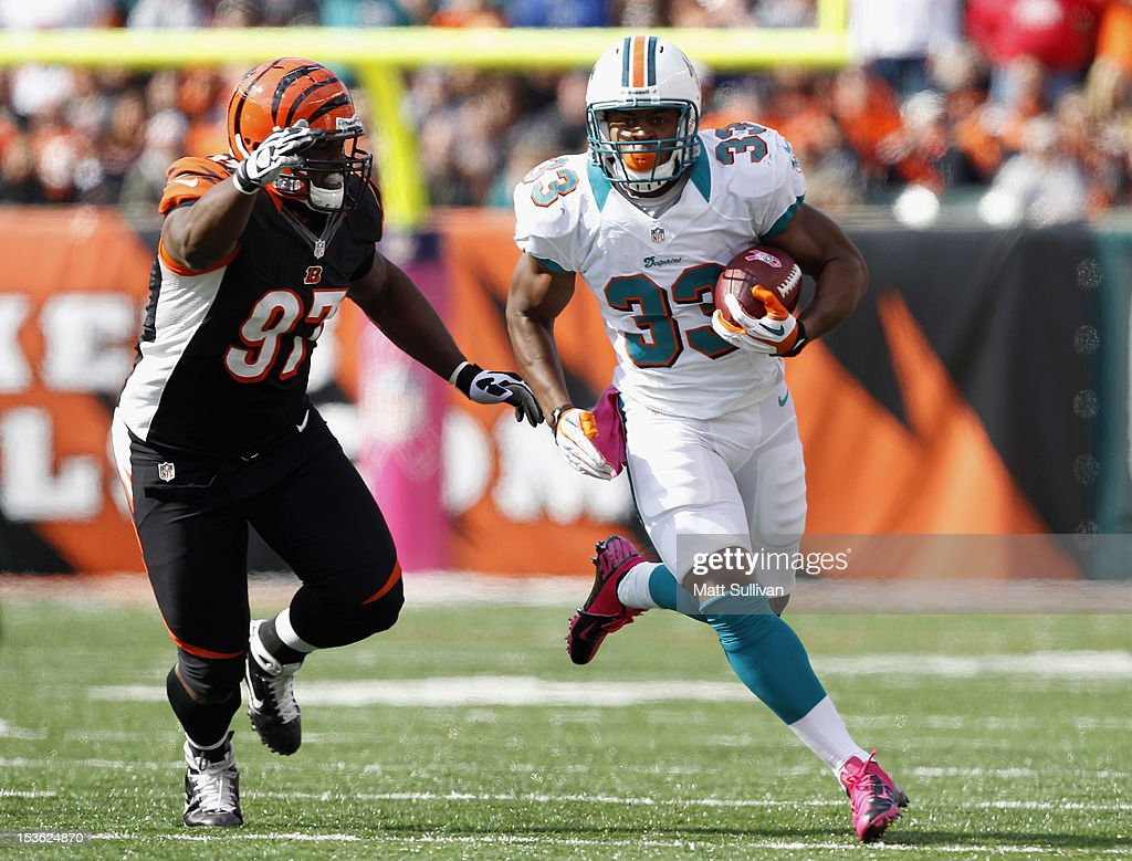 Running back Daniel Thomas #33 of the Miami Dolphins runs away from defensive tackle Geno Atkins #97 of the Cincinnati Bengals at Paul Brown Stadium on October 7, 2012 in Cincinnati, Ohio.