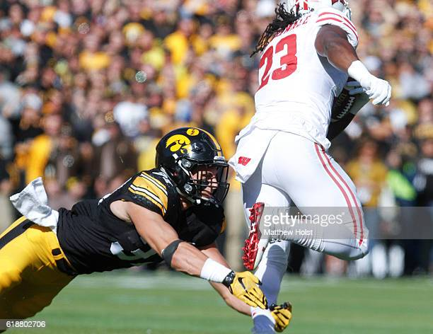 Running back Dare Ogunbowale of the Wisconsin Badgers breaks a tackle by defensive back Brandon Snyder of the Iowa Hawkeyes during the first quarter...