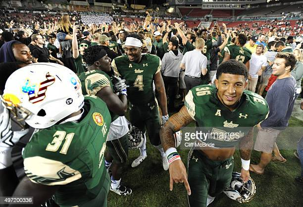 Running back Darius Tice of the South Florida Bulls and defensive back Nate Godwin of the South Florida Bulls celebrate on the field after the game...