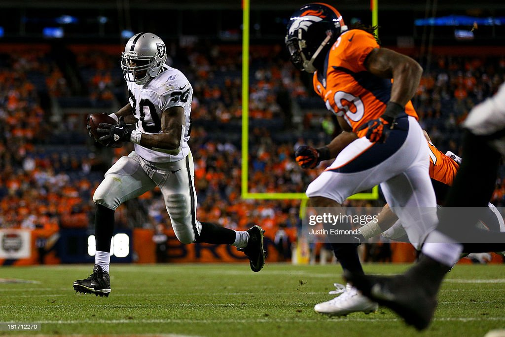 Running back Darren McFadden #20 of the Oakland Raiders runs for a touchdown late in the fourth quarter as safety David Bruton #30 of the Denver Broncos gives chase at Sports Authority Field Field at Mile High on September 23, 2013 in Denver, Colorado. The Broncos defeated the Raiders 37-21.