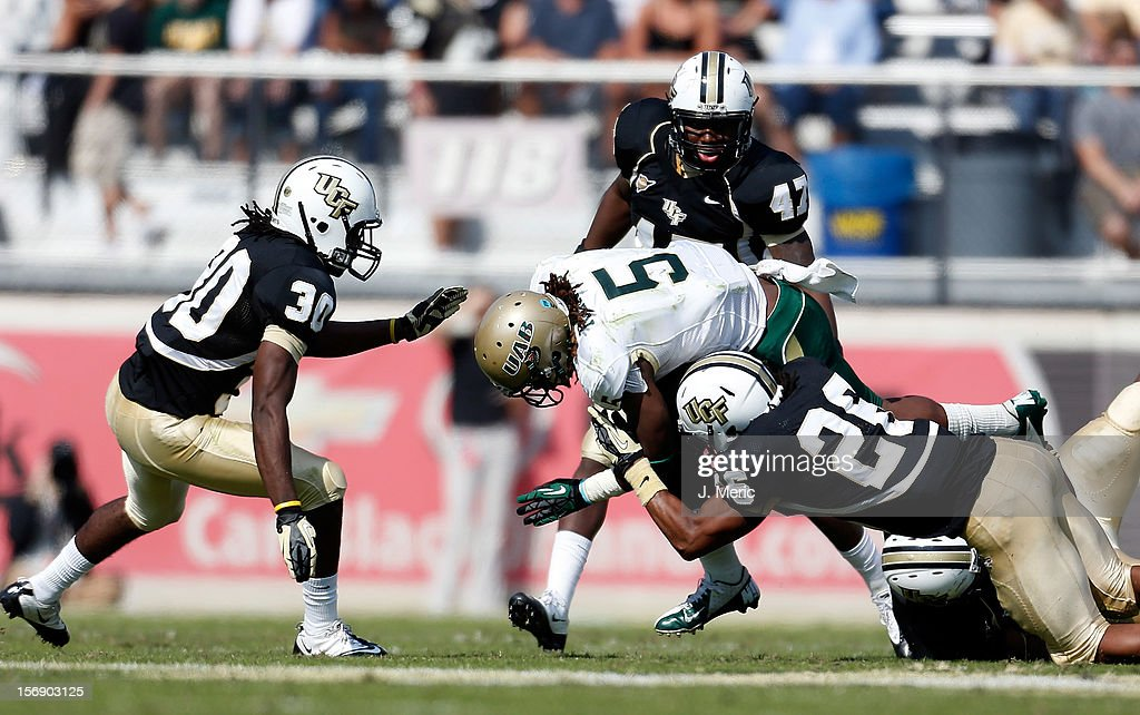 Running back Darrin Reaves #5 of the Alabama Birmingham Blazers is tackled by defender Clayton Geathers #26 of the Central Florida Knights during the game at Bright House Networks Stadium on November 24, 2012 in Orlando, Florida.