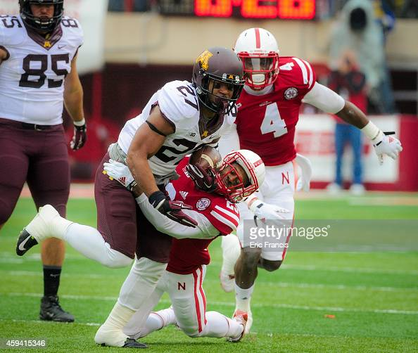 Running back David Cobb of the Minnesota Golden Gophers is wrapped up by cornerback Daniel Davie of the Nebraska Cornhuskers during their game at...