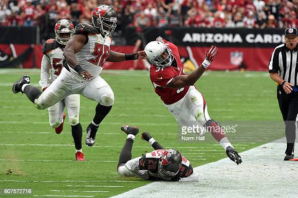 Running back David Johnson of the Arizona Cardinals is pushed out of bounds by defensive end Clinton McDonald and cornerback Vernon Hargreaves III of...
