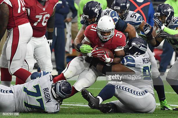 Running back David Johnson of the Arizona Cardinals is tackled by defensive tackle Ahtyba Rubin outside linebacker KJ Wright and defensive tackle...