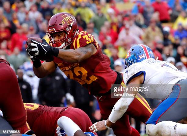 Running back David Montgomery of the Iowa State Cyclones dives into the end zone for a touchdown as safety Bryce Torneden of the Kansas Jayhawks...