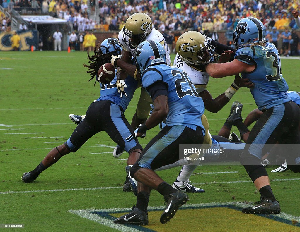 Running back David Sims #20 of the Georgia Tech Yellow Jackets stretches the ball over the goal line for a touchdown before safety <a gi-track='captionPersonalityLinkClicked' href=/galleries/search?phrase=Tre+Boston&family=editorial&specificpeople=7173024 ng-click='$event.stopPropagation()'>Tre Boston</a> #10 of the North Carolina Tar Heels knocks it out of his hands during the game at Bobby Dodd Stadium at Historic Grant Field on September 21, 2013 in Atlanta, Georgia.