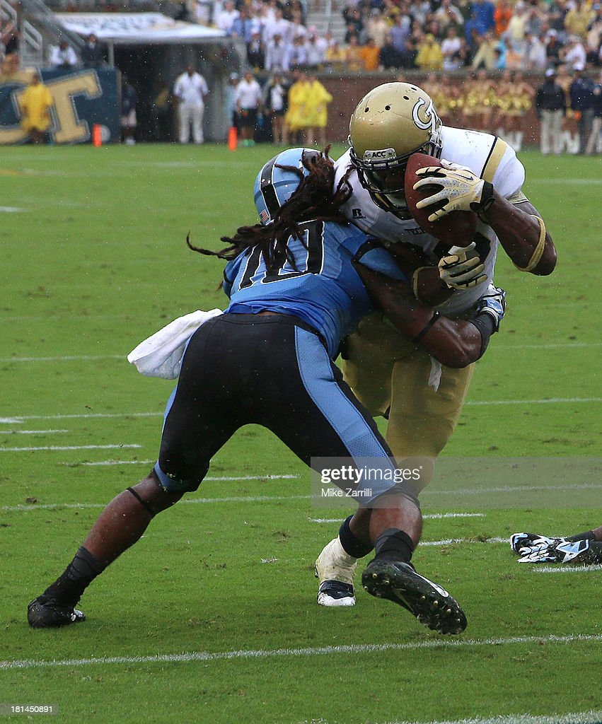 Running back David Sims #20 of the Georgia Tech Yellow Jackets stretches the ball over the goal line for a touchdown before safety Tre Boston #10 of the North Carolina Tar Heels knocks it out of his hands during the game at Bobby Dodd Stadium at Historic Grant Field on September 21, 2013 in Atlanta, Georgia.